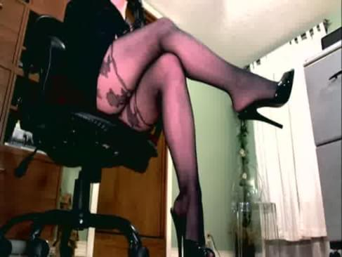 Femdom in pantyhose holding a leather paddle