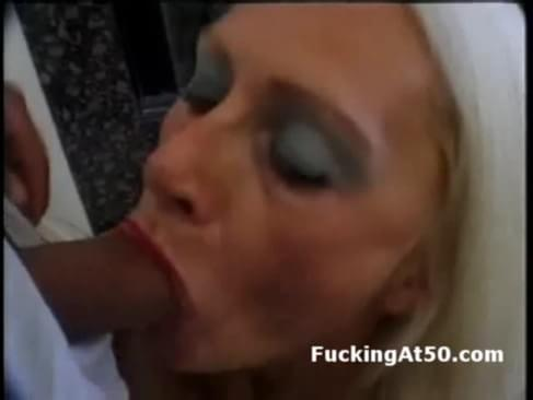 Horny old blonde woman wearing fishnets gives man a blowjob while a guy ...