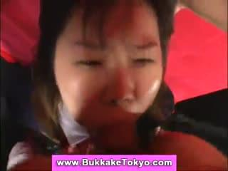 Video of an asian bukkake girl in kinky bondage taking a cum bath