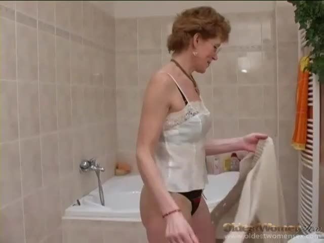 Mature strips from cardigan and shaves pussy