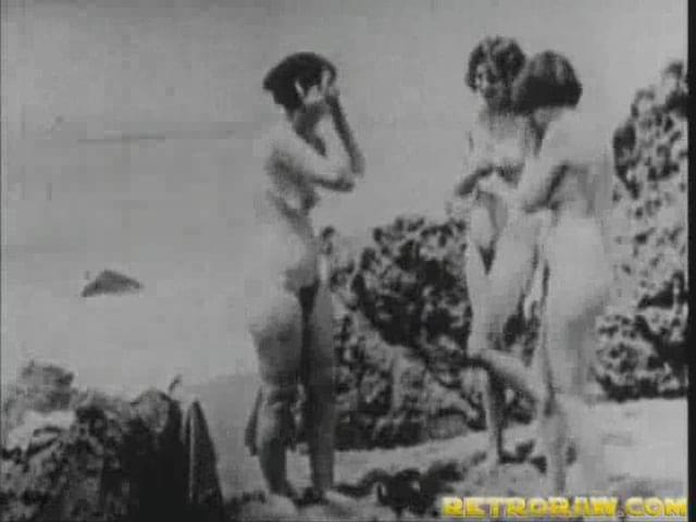 retro raw sex at the nude beach. a man in a suit is on a free beach watching ...